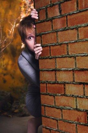 woman-hiding-behind-wall