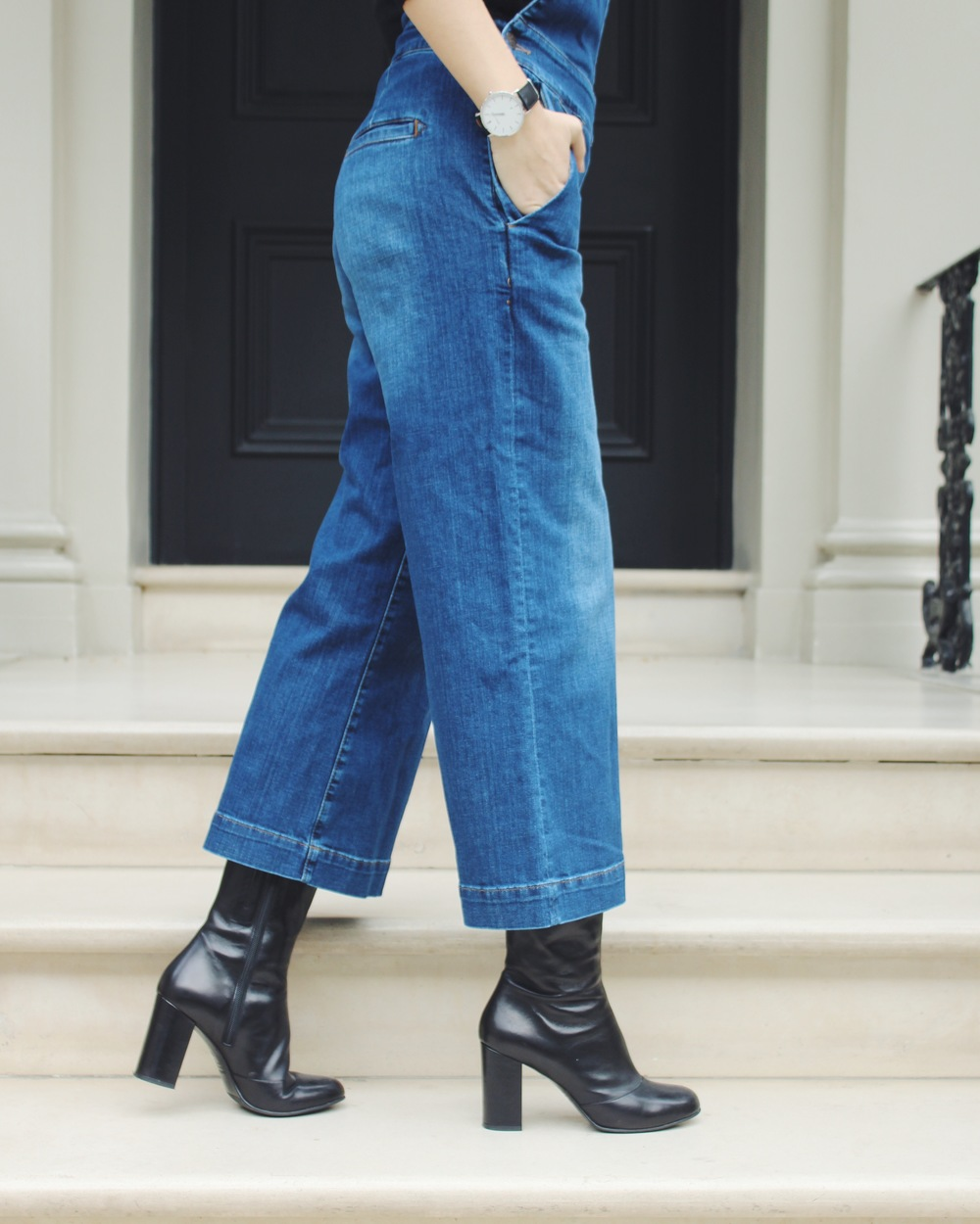 Arianna Trapani wearing the Donna Ida Ramona denim culotte pinafore paired with Baker boy hat, sock boots. Abbott Lyon watch.