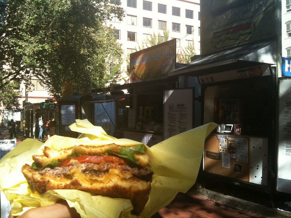 Eating a burger sandwiched between two grilled cheese sandwiches from a food truck in Portland, OR