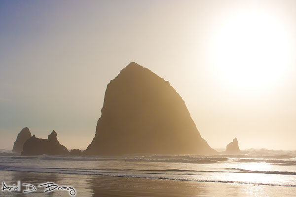 The sun glows behind Haystack Rock on Cannon Beach