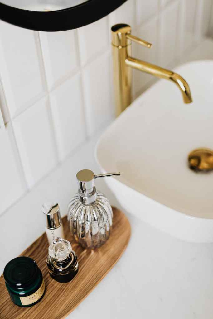 set of stylish cosmetic products placed near sink in bathroom