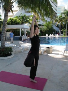 Tanya practicing Yoga beside the hotel pool in tree pose.