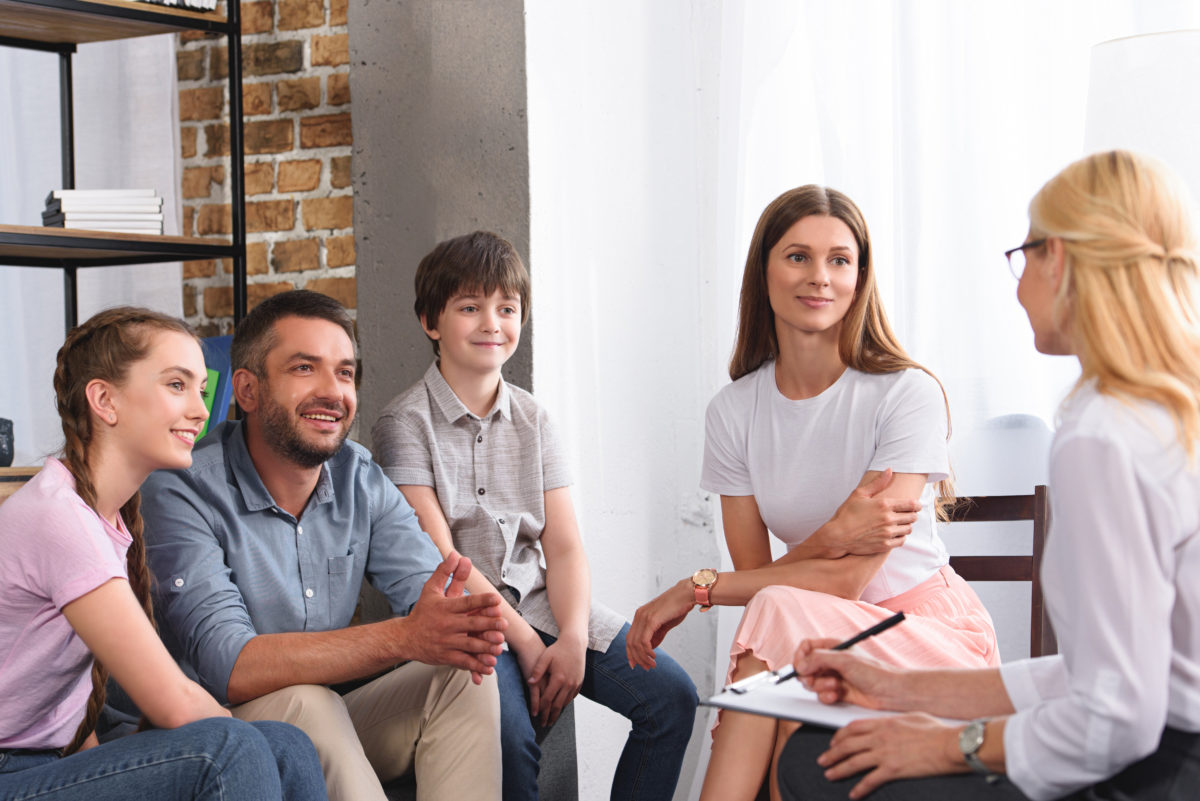 Happy Family Sitting On Therapy Session By Female