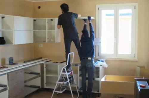 Two men are working together to install the shelves. The room is cluttered with materials to be used in the work.