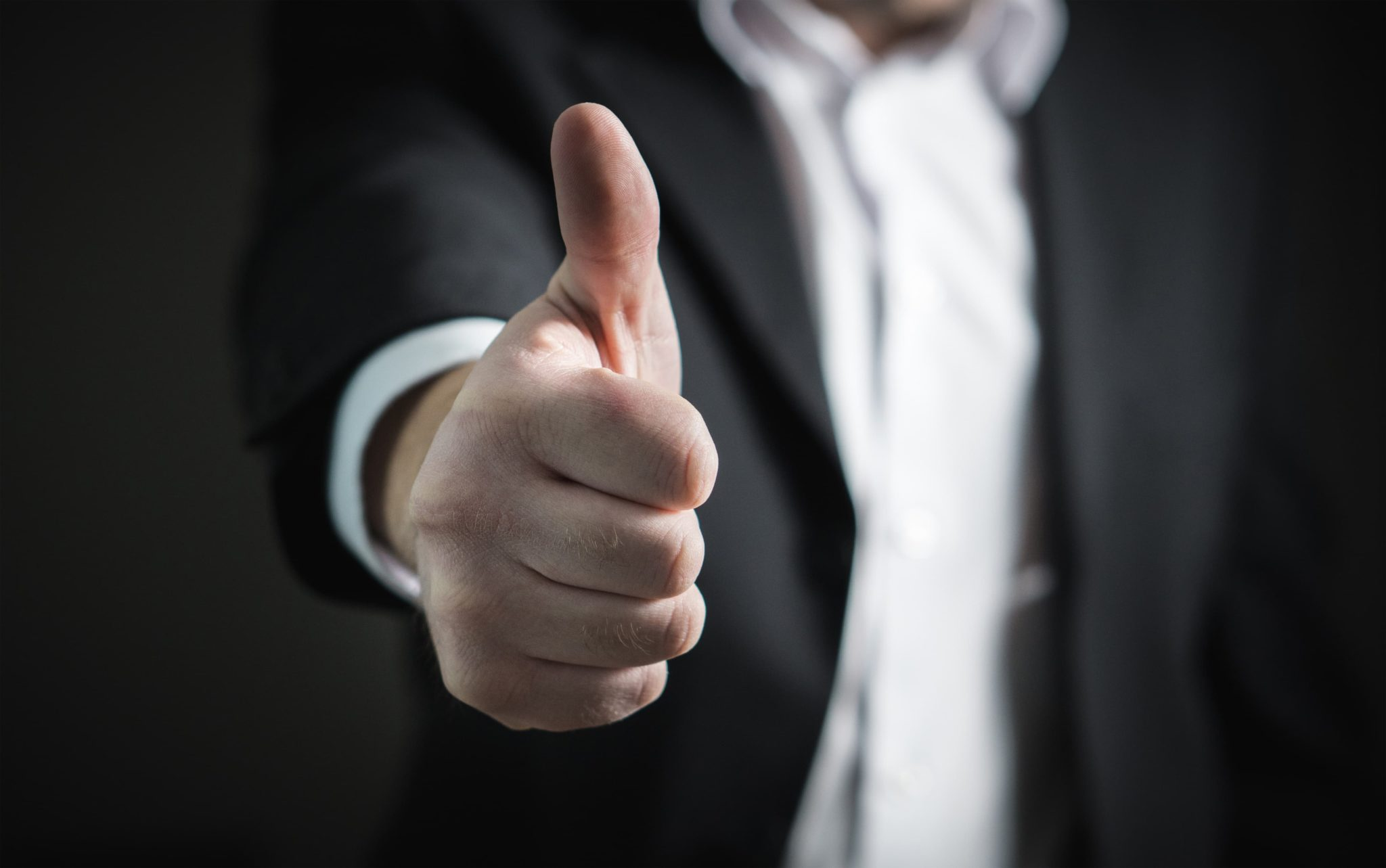 A man in a blazer jacket giving a thumbs up. It signals achievement in a field of work.