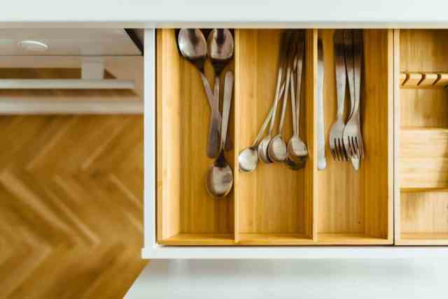 Various utensils are being stored in a drawer with an organizer. The organizer is made of wood to complement the modular cabinet and floor finishing.