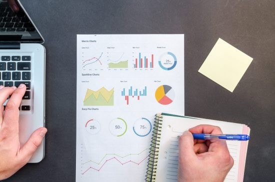 Graphs can be seen in a neat piece of paper on top of a desk. The spacious desk encourages productivity.