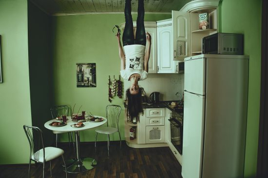 A lady standing on the ceiling looks disturbed. A cabinet remains open beside her in an otherwise organized kitchen.
