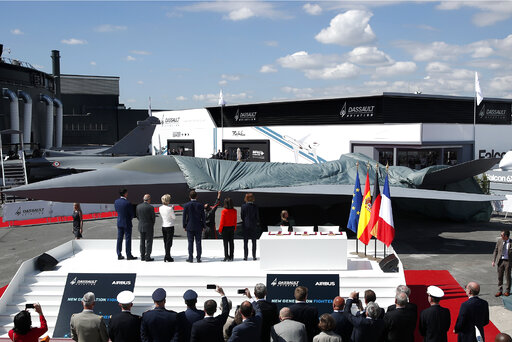 French President Emmanuel Macron, French Defence Minister Florence Parly and Eric Trappier, Chairman and CEO of Dassault Aviation, attend the 53rd International Paris Air Show at Le Bourget