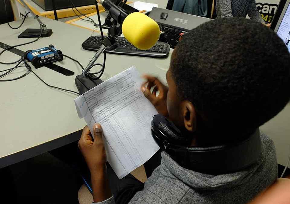 Photo - Un enfant enregistre une chronique radio
