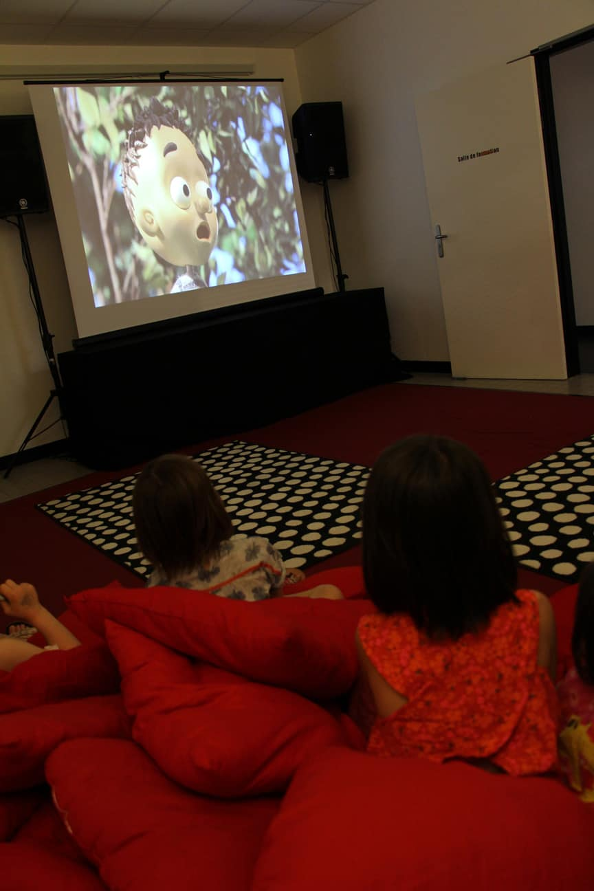 Photo d'enfants qui regardent un film projeté