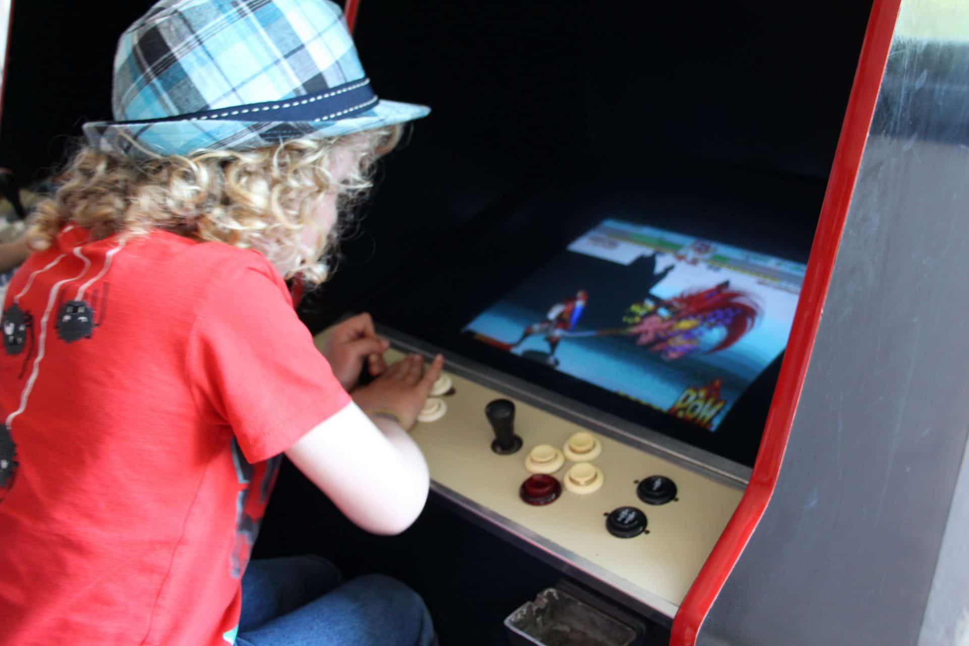 Photo d'une enfant jouant à une borne d'arcade
