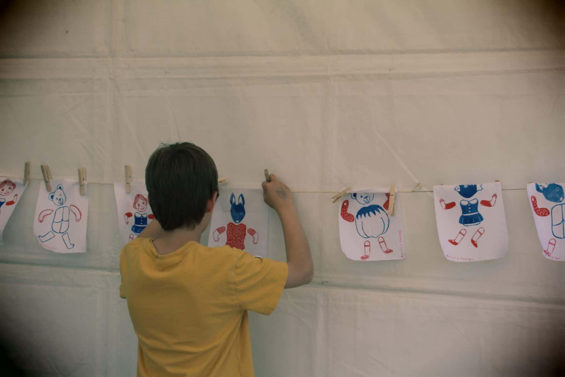 Photo - Un enfant accroche son dessin fait avec des tampons