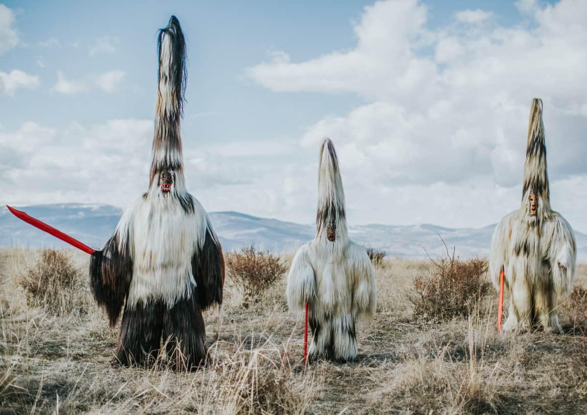 Photo de trois personnes déguisées avec des costumes couverts de long poils