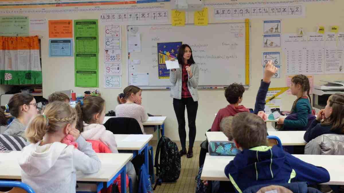 Photo - des enfant sont dans une classe avec leur institutrice