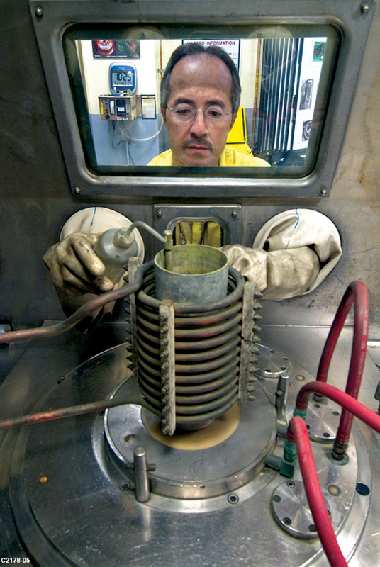 A technician at Los Alamos National Laboratory in New Mexico manipulates plutonium as part of the U.S. Stockpile Stewardship Program in 2005. Current plans call for expanding the production of plutonium pits at both Los Alamos and at the Savannah RIver Site in South Carolina. (Photo: U.S. Energy Department)