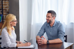 smiling man talking to female psychiatrist while she writing in clipboard at office