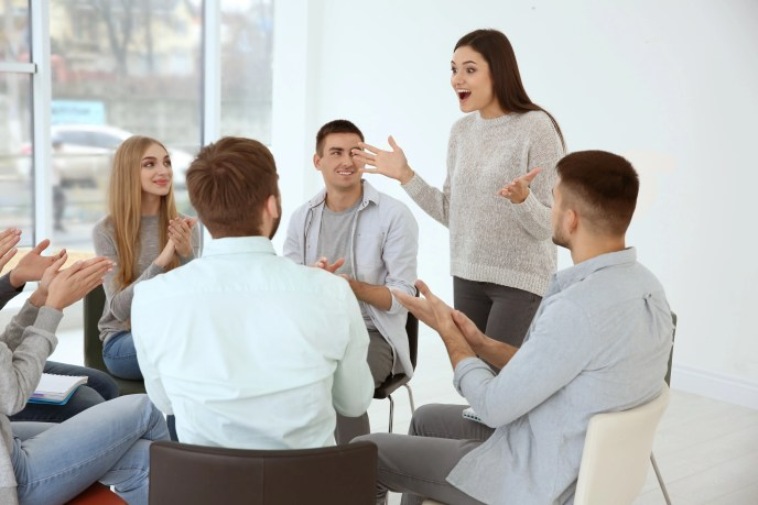 Young woman talking about her feelings during group therapy, indoors