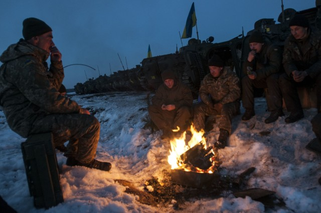 Crew members of a Ukrainian BMP-2 armored vehicle warm themselves by a fire before returning to the firing line for a night fire exercise at the International Peacekeeping and Security Center, near Yavoriv, Ukraine, on Feb. 16.