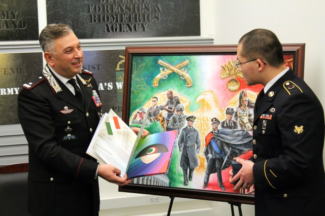 Gen. Tullio Del Sette, left, who heads the Italian Carabinieri Corps, presents a book of graphic illustrations as a gift to Army Spc. Zee H. Leung, right, a multimedia illustrator with the Army Multimedia and Visual Information Directorate. Just prior, Leung and the Italian general unveiled a painting which highlights the relationship between the U.S. Army military police corps and the military police corps of the Italian military. The painting, produced by Leung, was a gift to the Italians by the U.S. Army's Provost Marshal. The exchange took place in November 2016 at the Pentagon.