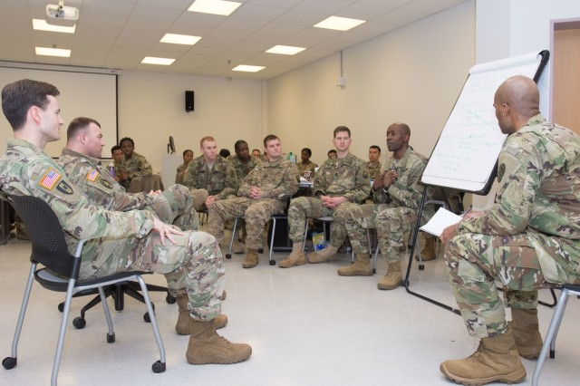 LANDSTUHL, Germany - Capt. John O. Okomu, social worker, 254th Medical Detachment, Combat Operational Stress Control, briefs his group's unit assessment to Lt. Col. Robert J. Parish, neuropsychologist and commander, 254th COSC and Sgt 1st Class Clayton Cope, detachment sergeant, at training by the U.S. Army Medical Department Center and School Combat and Operational Stress Control Mobile Training Team on Mar. 2, 2017. (U.S. Army photo by Capt. Jerome Ferrin, 30th Medical Brigade Public Affairs)