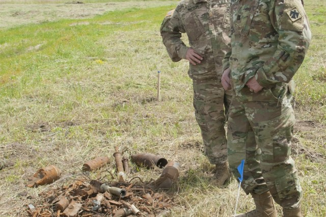 Maj. Christopher Watson, 45th Infantry Brigade Combat Team and Joint Multinational Training Group-Ukraine range operations officer, and Capt. Montana Dugger, 45th IBCT and JMTG-U engineer, evaluate the progress that has been made toward clearing areas of unexploded ordinance at the Yavoriv Combat Training Center on the International Peacekeeping and Security Center near Yavoriv, Ukraine on June 16. Range improvement operations are currently in progress to clear several areas on the IPSC of unexploded ordinance. Four civilian demining teams, contracted by the U.S. Army through the Joint Multinational Training Group-Ukraine, are working toward the goal of clearing 1,800 hectares of UXO by 2018.
