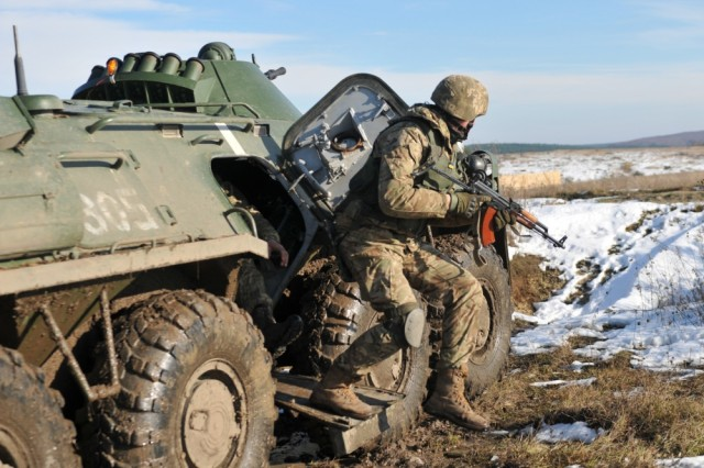 A Ukrainian Soldier from the 1st Battalion, 80th Airmobile Brigade jumps out of a BTR armored vehicle during a suppressive fire training exercise led by U.S. Soldiers assigned to 6th Squadron, 8th Cavalry Regiment, 2nd Infantry Brigade Combat Team, 3rd Infantry Division, at the International Peacekeeping and Security Center, Nov. 18, 2016. Range improvement operations are currently in progress to clear several areas on the IPSC of UXO. Four civilian demining teams, contracted by the U.S. Army through the Joint Multinational Training Group-Ukraine, are working toward the goal of clearing 1,800 hectares of UXO by 2018.