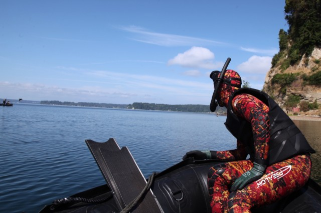 """A safety swimmer keeps on eye on a team from 3rd Battalion, 1st Special Forces Group (Airborne) during a competition held during """"Dragon Week"""" on Joint Base Lewis-McChord, Wash., June 28. Dragon Week consisted of airborne operations, maritime operations, patrol lanes, a stress shoot, and medical evaluations to test readiness at the battalion level."""