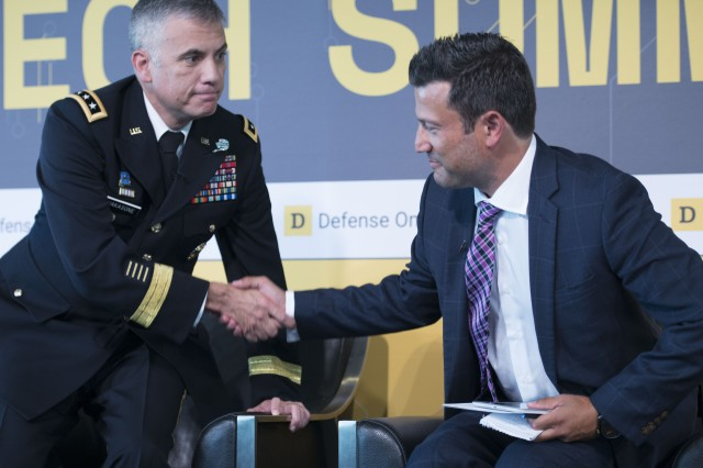 Lt. Gen. Paul Nakasone, chief of Army Cyber command, shakes hands with Defense One Executive Editor Kevin Baron at the Newseum in Washington, D.C., July 13. Nakasone participated in a live panel event and fielded questions from the public at the 2017 Defense One Tech Summit.