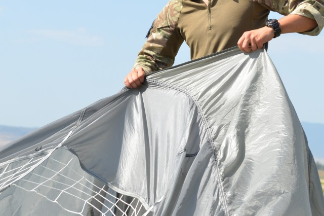 VAZIANI TRAINING AREA, Georgia - British soldier Pvt. Josh Street, 2nd Battalion, Parachute Regiment (2nd PARA), 16th Air Assault Brigade, Essex, England, extends the MC-6 parachute, at the drop zone on Vaziani Training Area, Georgia, Aug. 7, 2017. Street prepares the parachute for collection. The red tape signifies first-time jumpers. The 2nd PARA is currently in the Republic of Georgia to participate in Exercise Noble Partner. Noble Partner is a multinational, U.S. Army Europe-led exercise conducting home station training for the Georgian light infantry company designated for the NATO Response Force. (U.S. Army photo by Sgt. Shiloh Capers)