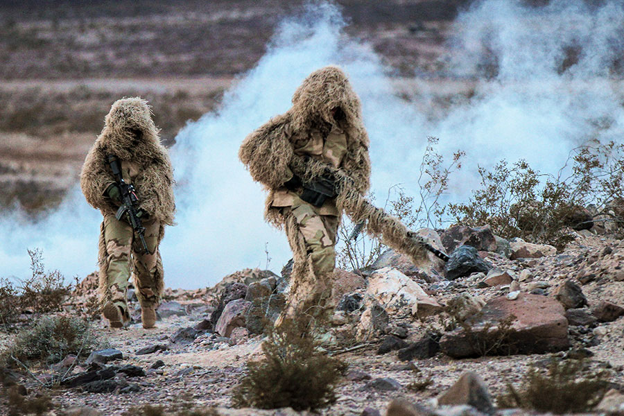 U.S. Army snipers wearing special camouflage train in a life-fire exercise.