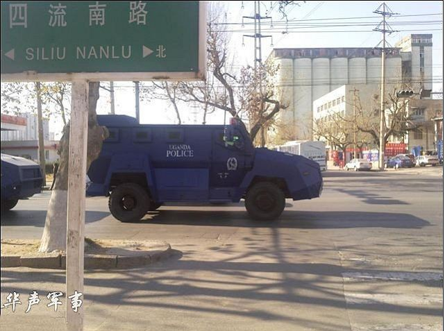 """A picture take in China shows a convoy of anti-riot armoured vehicle on the way to be transfer in Africa. On the sides of the vehicles it is written """"Uganda Police""""."""
