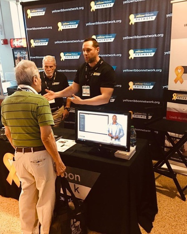 John Pickens (L), executive director of VeteransPlus and the Yellow Ribbon Network, and Kyle Vanschoyck (R), director of the Yellow Ribbon Network, speak with a veteran at a Homeless Veterans Outreach event in Florida. (Photo provided by John Pickens)