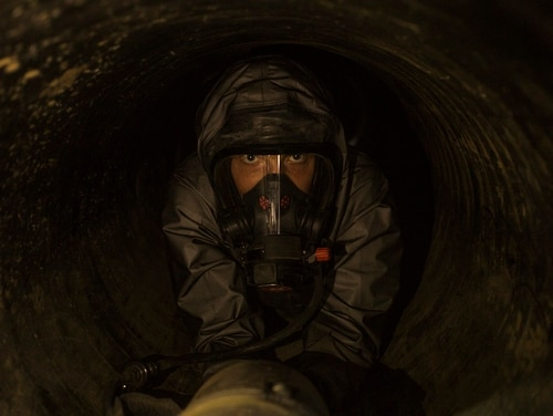 Marine Cpl. Seth White, a chemical, biological, radiological and nuclear defense specialist with the 11th Marine Expeditionary Unit, crawls through an underground tunnel while wearing a Level-C hazmat suit on Camp Pendleton, California, Oct. 3, 2018. (Cpl. Adam Dublinske/Marine Corps)
