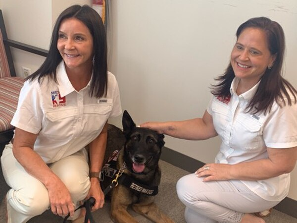 Kristen Maurer (L), president and founder of Mission K9 Rescue, and Louisa Kastner (R), the nonprofit's vice president, pose with Zero, a retired military dog who the organization is helping get adopted. (Joshua Axelrod/Military Times)