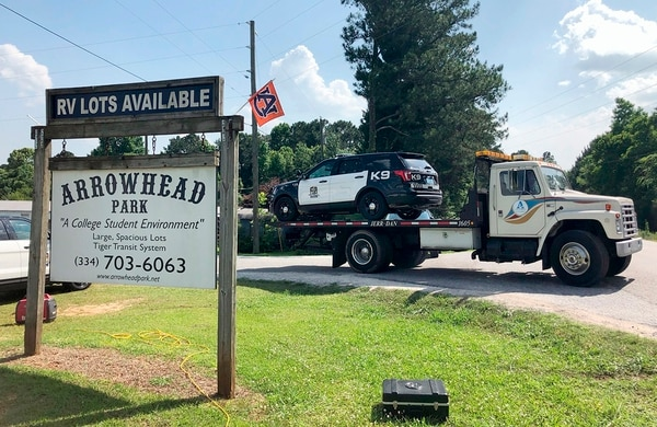 A tow truck removes a police car from a mobile home park, Monday, May 20, 2019, in Auburn, Ala., where three police officers were shot late Sunday. Authorities say a man opened fire on police responding to a domestic call late Sunday, killing one officer and wounding two others. (Blake Paterson/AP)