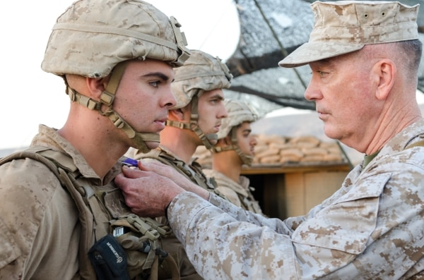 Chairman of the Joint Chiefs of Staff Gen. Joseph Dunford presents Marine Cpl. Adam Seanor with the Purple Heart during a ceremony at Kara Soar Base, Makhmur, Iraq, April 22, 2016. (Staff Sgt. Peter J. Berardi/Army)