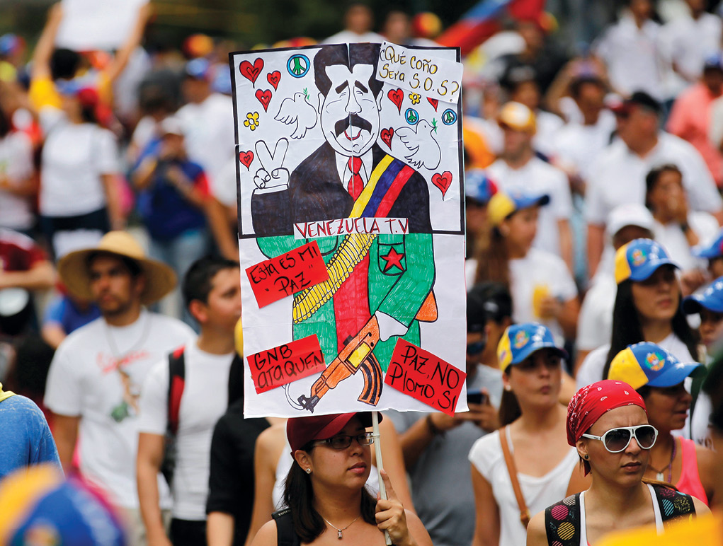 """An antigovernment protester holds a poster with a caricature of Venezuela's President Nicolas Maduro 2 March 2014 during a rally against his government in Caracas. The poster reads, """"What the hell does SOS mean?,"""" """"Peace no, bullets yes."""" Subsequently, thousands of antigovernment demonstrators marched in the capital trying to keep up the momentum during months of protests demanding Maduro's resignation. (Photo by Jorge Silva, Reuters)"""