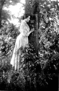 Helen Keller leaning against a tree. By White, 1907.