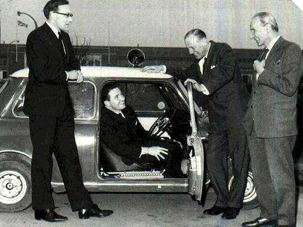 33 EJB, the car that won the 1964 Monte Carlo rally, pictured with (left to right) its crew of Henry Liddon and Paddy Hopkirk, BMC chairman George Harriman and Alec Issigonis.