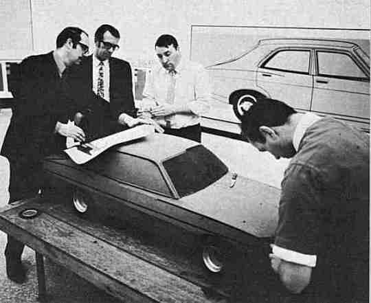 The first quarter scale clay model is worked upon by (right to left) lead modeller, Ray Key, exteriors modelling supervisor, Matt Muncaster, exterior chief stylist Reg Myatt and Roy Axe.