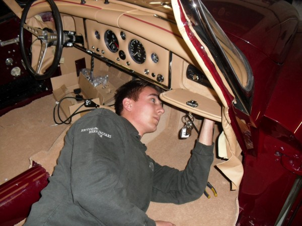 Electrical apprentice Tom Smallman (21) from Bridgnorth, Shropshire, who works for classic car restorers Classic Motor Cars Ltd, fitting some crossover for the audio speakers in a Jaguar XK150 roadster.