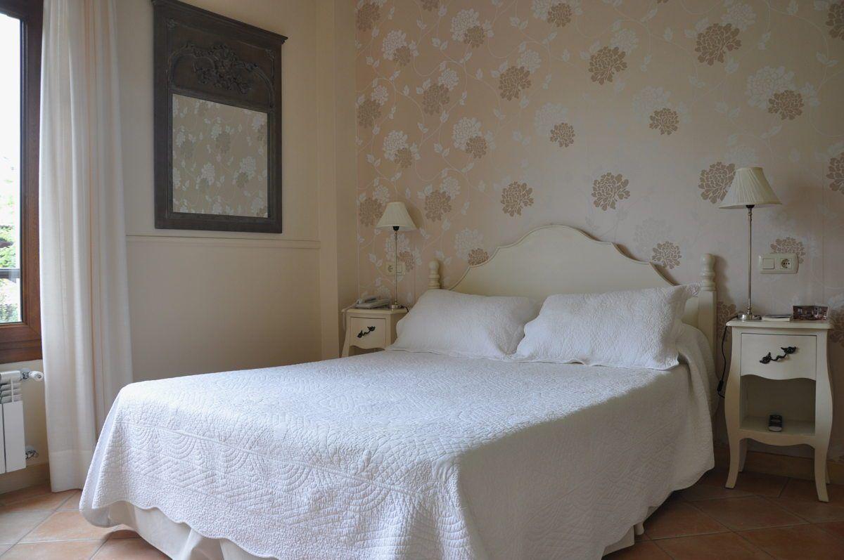 Habitación luminosa en tonos blancos con vistas al jardín en Hotel Rural Arpa de Hierba