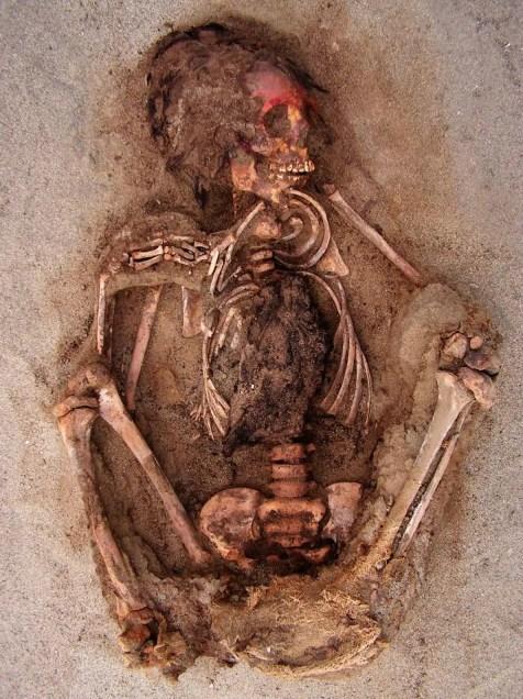 Durante la ceremonia, a muchos de los niños se les embadurnó el rostro con un pigmento rojo a base de cinabrio antes de que se les abriera el pecho, probablemente para quitarles el corazón. Las llamas de los sacrificios parecen haber tenido el mismo destino. FOTOGRAFÍA DE GABRIEL PRIETO