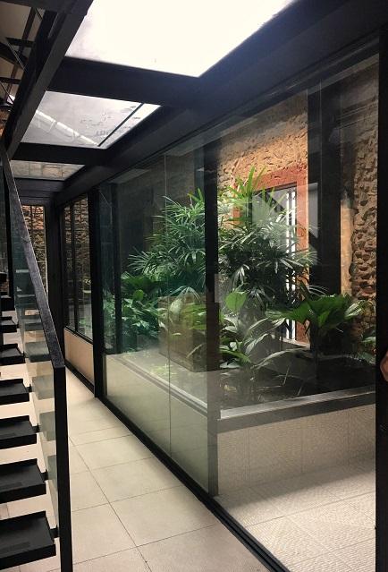 Puerta de vidrio canto a canto, hoja motorizada de más de 4 mts.