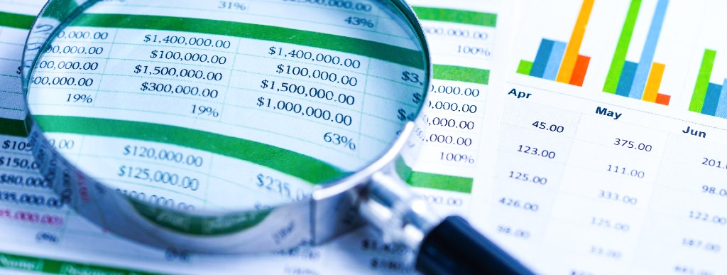 magnifying glass looking at financial statements to highlight the difficulty of finding the right business cpa