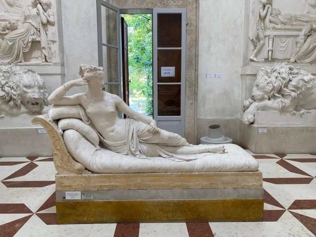 Sculpture of a woman lounging on a sofa as a goddess