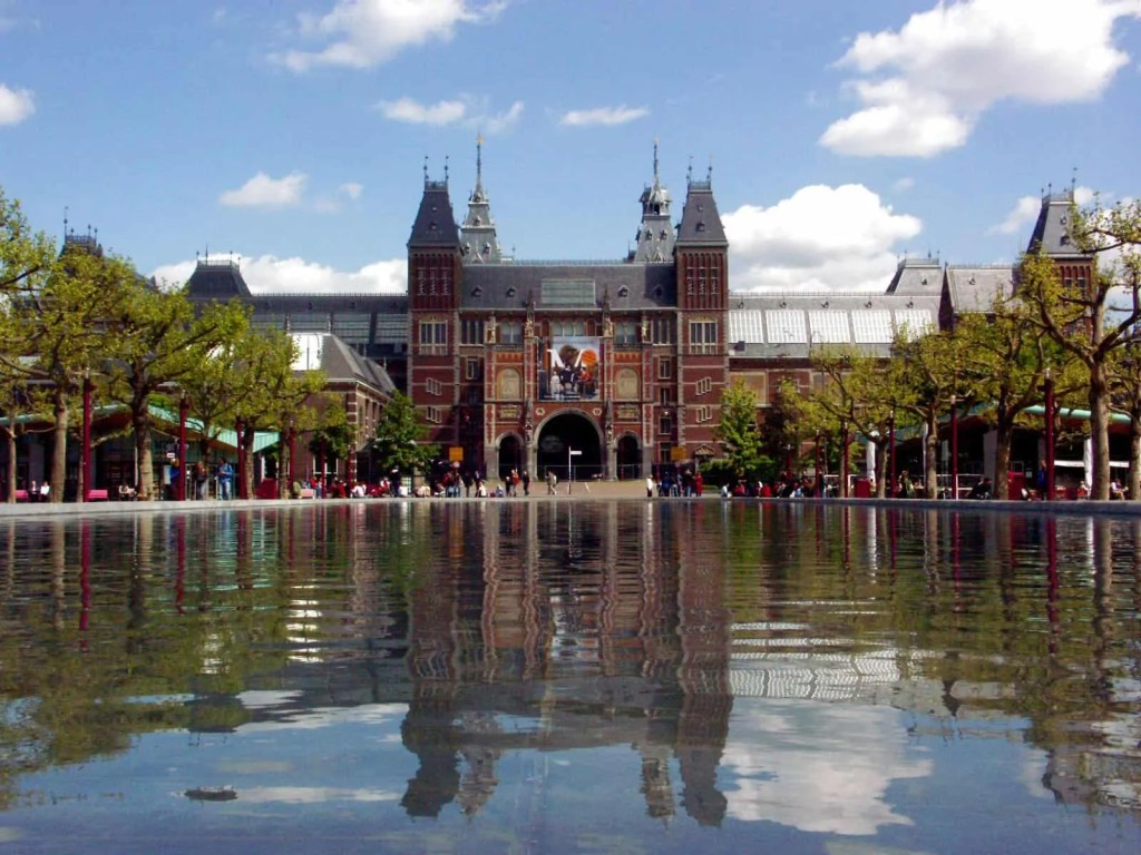 The red brick exterior of the Rijksmuseum in Amsterdam reflected in a reservoir Art World Roundup