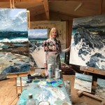 An artist stands by her paintings in her studio in Scotland art World Roundup