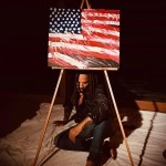 """Lenny Kravitz sits beneath a painting of the American flag to be part of """"Show Me the Signs"""""""